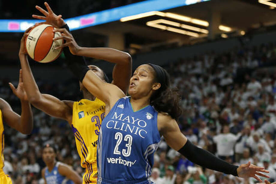 Minnesota Lynx forward Maya Moore (23) tries to grab a rebound from Los Angeles Sparks forward Nneka Ogwumike (30) in the second half of Game 1 of the WNBA basketball finals Sunday, Oct. 9, 2016, in Minneapolis. (AP Photo/Stacy Bengs)