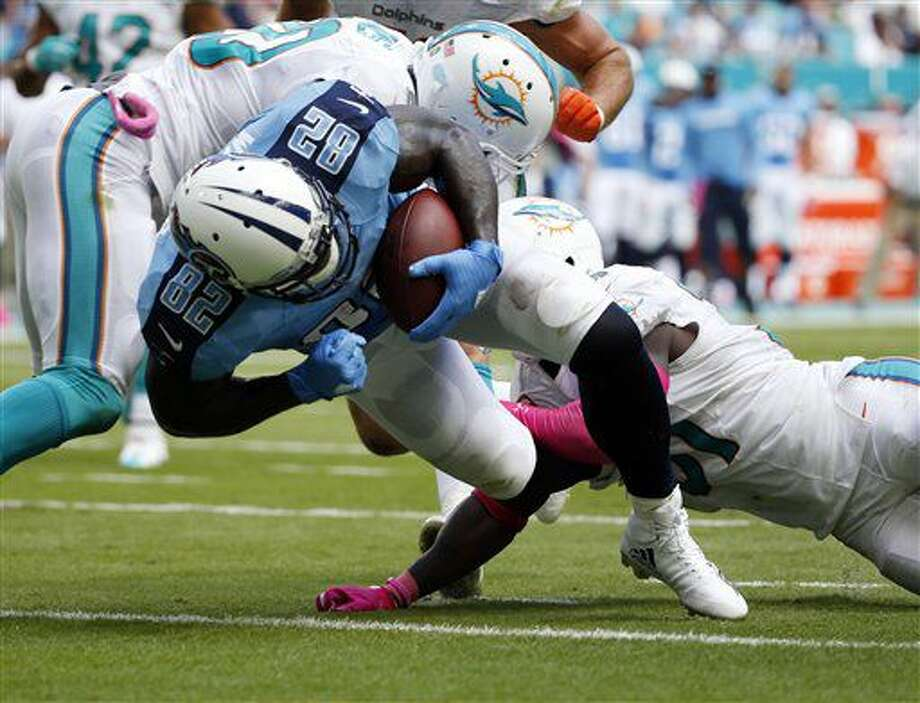 Tennessee Titans tight end Delanie Walker (82) scores a touchdown as Miami Dolphins free safety Michael Thomas (31) and free safety Reshad Jones (20) attempt to stop him, during the first half of an NFL football game, Sunday, Oct. 9, 2016, in Miami Gardens, Fla. (AP Photo/Wilfredo Lee)