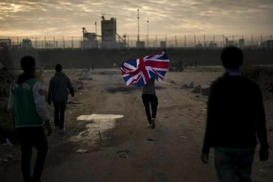 "FILE - In this Tuesday, Oct. 25, 2016 file photo a man runs with a British flag inside a makeshift camp known as ""the jungle"" near Calais, northern France. France began the mass evacuation Monday of the makeshift migrant camp known as ""the jungle,"" a mammoth project to erase the humanitarian blight on its northern border, where thousands fleeing war or poverty have lived in squalor, most hoping to sneak into Britain. (AP Photo/Emilio Morenatti, File)"