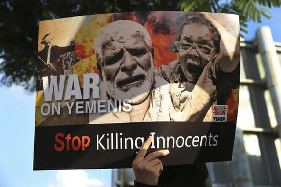 A Lebanese supporter of the Iranian-backed Shiite Hezbollah group, holds a placard during a protest to show their solidarity with Yemen's Shiite rebels, known as Houthis, in front the United Nations headquarters, in Beirut, Lebanon, Monday, Oct. 10, 2016. (AP Photo/Hussein Malla)