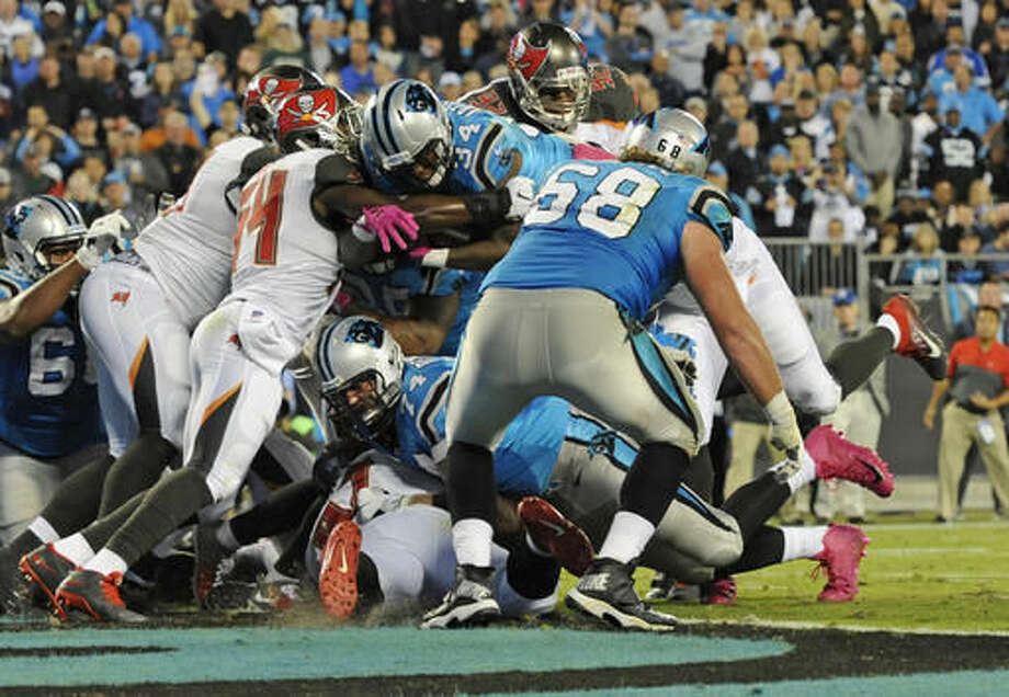 Carolina Panthers' Cameron Artis-Payne (34) dives over the goal line for a touchdown against the Tampa Bay Buccaneers in the second half of an NFL football game in Charlotte, N.C., Monday, Oct. 10, 2016. (AP Photo/Mike McCarn)