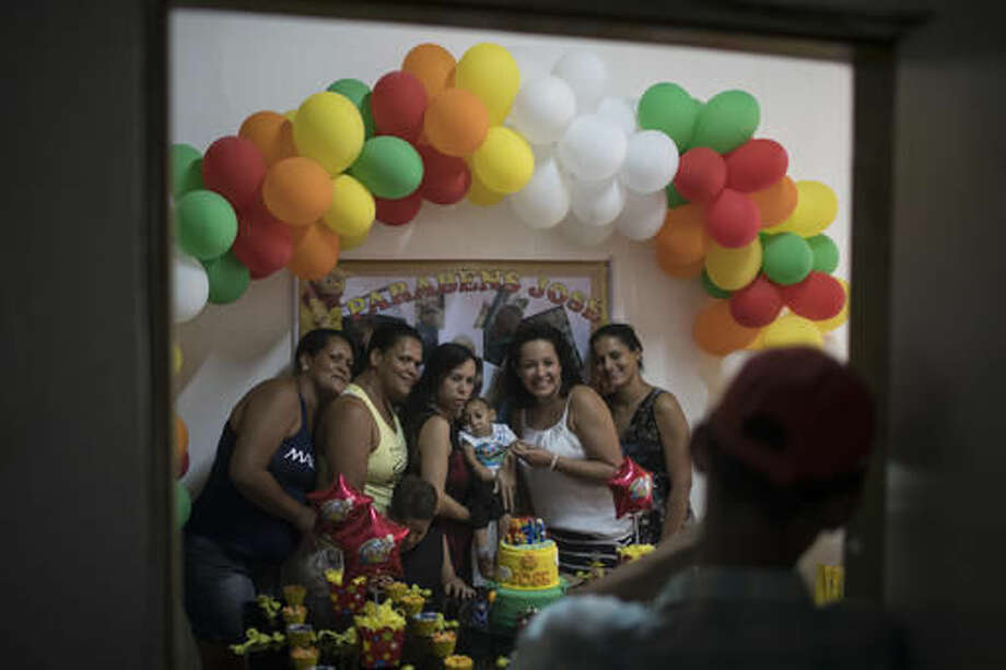 In this Sept. 27, 2016 photo, relatives and hospital staff pose for a photo with Jose Wesley Campos during his 1-year birthday party at home in Bonito, Pernambuco state, Brazil. Learning how to feed is Jose's latest struggle as medical problems mount for him and many other infants born with small heads to mothers infected with the Zika virus in Brazil. (AP Photo/Felipe Dana)