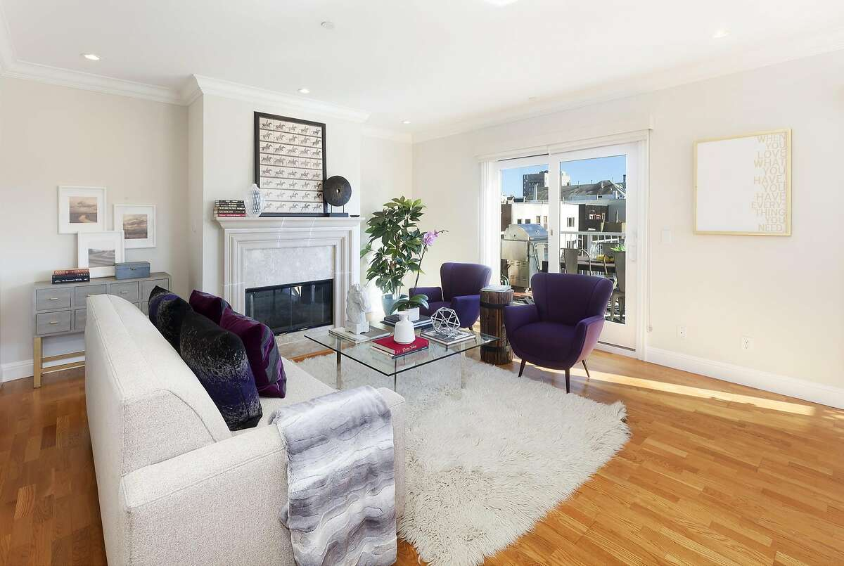 Hardwood flooring and a gas fireplace grace the living room of the Presidio Heights condo.