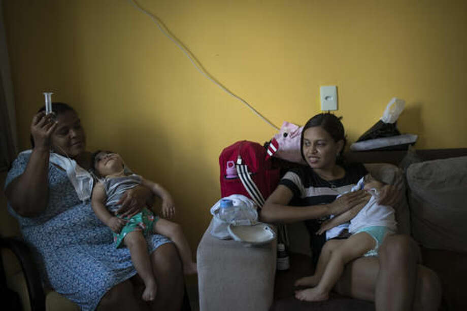 In this Oct. 1, 2016 photo, Daniele Ferreira dos Santos and her son Juan Pedro, right, sit next to Heloisa Dias who feeds her grandson Arthur Conceicao during his one-year birthday party in Recife, Pernambuco state, Brazil. Arthur, who was born with microcephaly, has started taking high-calorie formula through a tube after he appeared to choke during meals. (AP Photo/Felipe Dana)
