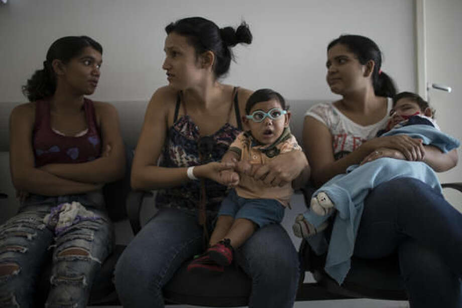 In this Sept. 27, 2016 photo, babies born with microcephaly Alexandro Julio, center, and Pedro Henrique, wait for their physical therapy session at the UPAE hospital in Caruaru, Pernambuco state, Brazil. A year after a spike in the number of newborns with the defect known as microcephaly, doctors and researchers have seen many of the babies develop swallowing difficulties, epileptic seizures and vision and hearing problems. (AP Photo/Felipe Dana)