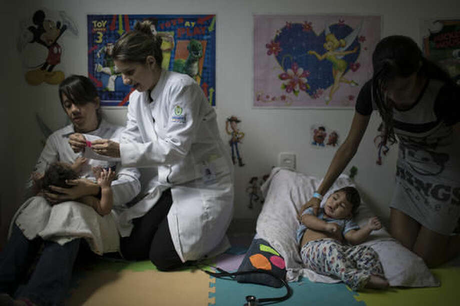 In this Sept. 27, 2016 photo, physical therapist Camilla Costa, left, and speech therapist Amora Marins apply Kinesio Tape on Luiza as Victoria Leticia, right, holds her son Lucas Matheus, during a physical therapy session for babies born with microcephaly at the UPAE hospital in Caruaru, Pernambuco state, Brazil. A year after a spike in the number of newborns with microcephaly, doctors and researchers have seen many of the babies develop swallowing difficulties, epileptic seizures and vision and hearing problems. (AP Photo/Felipe Dana)