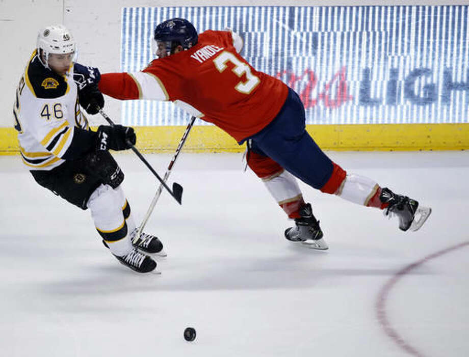 Boston Bruins center David Krejci (46) and Florida Panthers defenseman Keith Yandle (3) battle for the puck during the first period of an NHL hockey game, Tuesday, Nov. 1, 2016, in Sunrise, Fla. (AP Photo/Wilfredo Lee)
