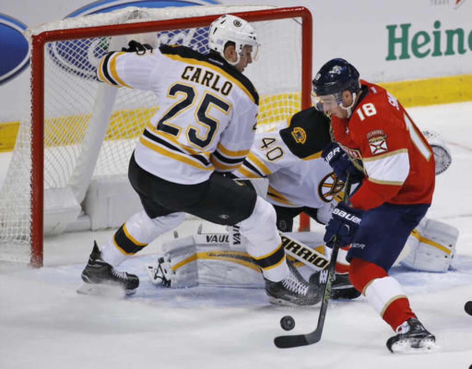 Florida Panthers right wing Reilly Smith (18) attempts a shot against Boston Bruins defenseman Brandon Carlo (25) and goalie Tuukka Rask (40) during the first period of an NHL hockey game, Tuesday, Nov. 1, 2016, in Sunrise, Fla. (AP Photo/Wilfredo Lee)