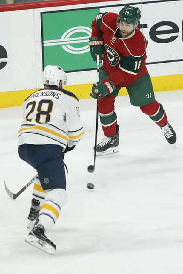 Minnesota Wild's Jason Zucker looks to pass the puck away from Buffalo Sabres' Zemgus Girgensons in the first period of an NHL hockey game Tuesday, Nov. 1, 2016, in St. Paul, Minn. (AP Photo/Stacy Bengs)