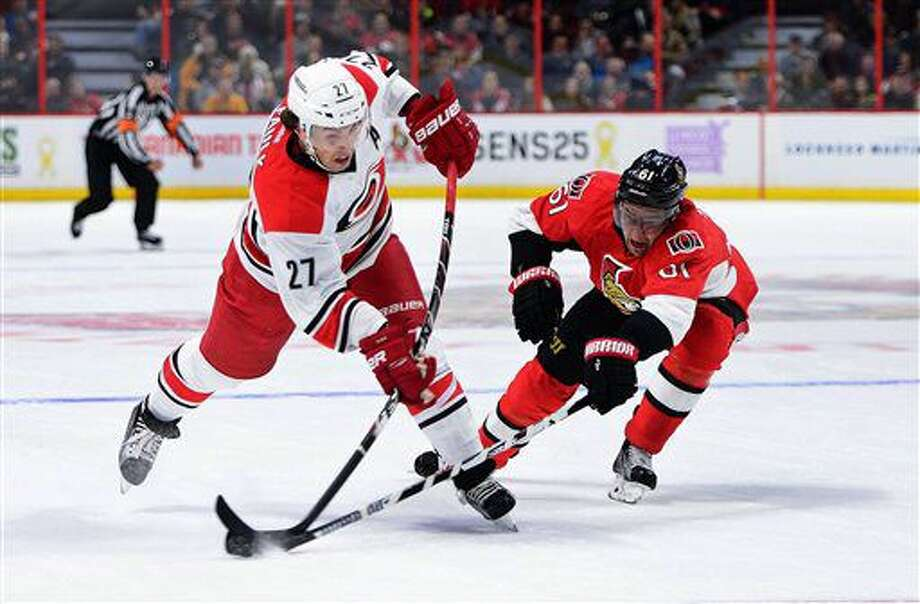 Ottawa Senators' Mark Stone, right, blocks a shot from Carolina Hurricanes' Justin Faulk during the first period of an NHL hockey game in Ottawa, Tuesday, Nov. 1, 2016. (Sean Kilpatrick/The Canadian Press via AP)