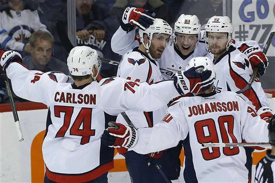 Washington Capitals' John Carlson (74), Brooks Orpik (44), Jay Beagle (83), Marcus Johansson (90) and Evgeny Kuznetsov (92) celebrate Beagle's game winning goal against the Winnipeg Jets during the third period of an NHL hockey game in Winnipeg, Manitoba, Tuesday, Nov. 1, 2016. The Capitals won 3-2. (John Woods/The Canadian Press via AP)