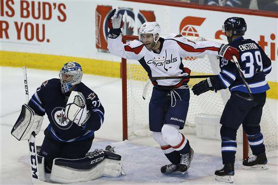Washington Capitals' Brett Connolly (10) celebrates Karl Alzner's goal on Winnipeg Jets goaltender Connor Hellebuyck (37) as Toby Enstrom (39) watches during the first period of an NHL hockey game Tuesday, Nov. 1, 2016, in Winnipeg, Manitoba. (John Woods/The Canadian Press via AP)