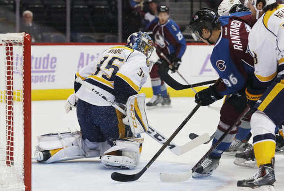 Nashville Predators goalie Pekka Rinne, left, of Finland, stops a shot off the stick of Colorado Avalanche right wing Mikko Rantanen, of Finland, during the first period of an NHL hockey game Tuesday, Nov. 1, 2016, in Denver. (AP Photo/David Zalubowski)