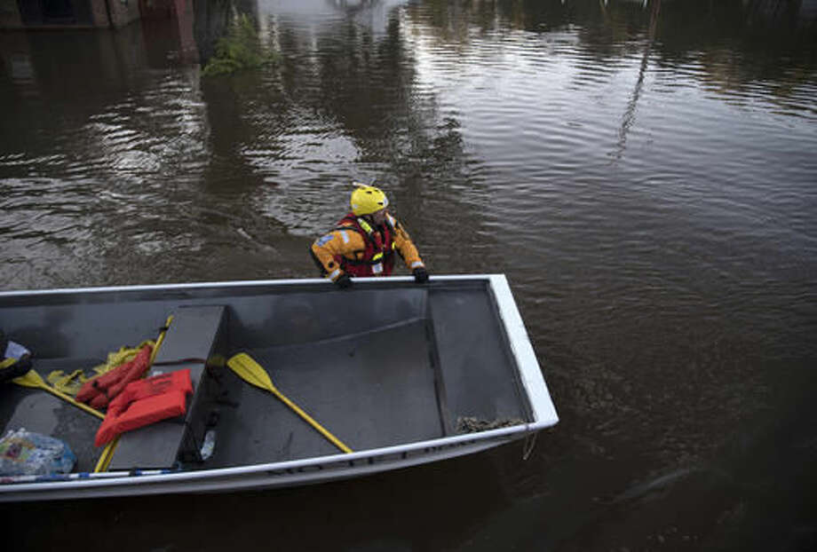 A swift water rescue team member guides a boat through floodwaters caused by rain from Hurricane Matthew in Lumberton, N.C., Monday, Oct. 10, 2016. (AP Photo/Mike Spencer)