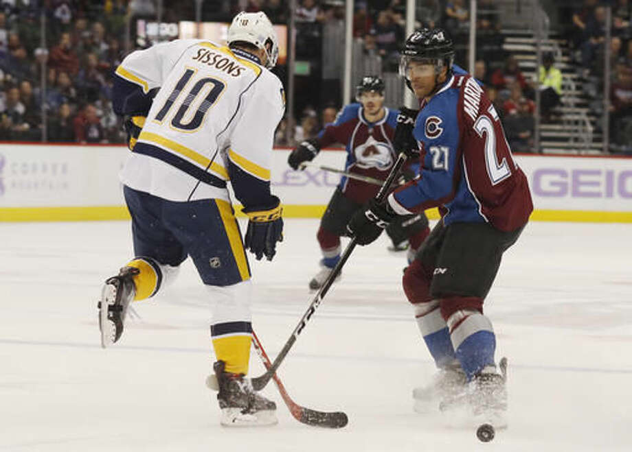Nashville Predators center Colton Sissons, left, deflects a shot off the stick of Colorado Avalanche left wing Andreas Martinsen, of Norway, during the first period of an NHL hockey game Tuesday, Nov. 1, 2016 in Denver. (AP Photo/David Zalubowski)