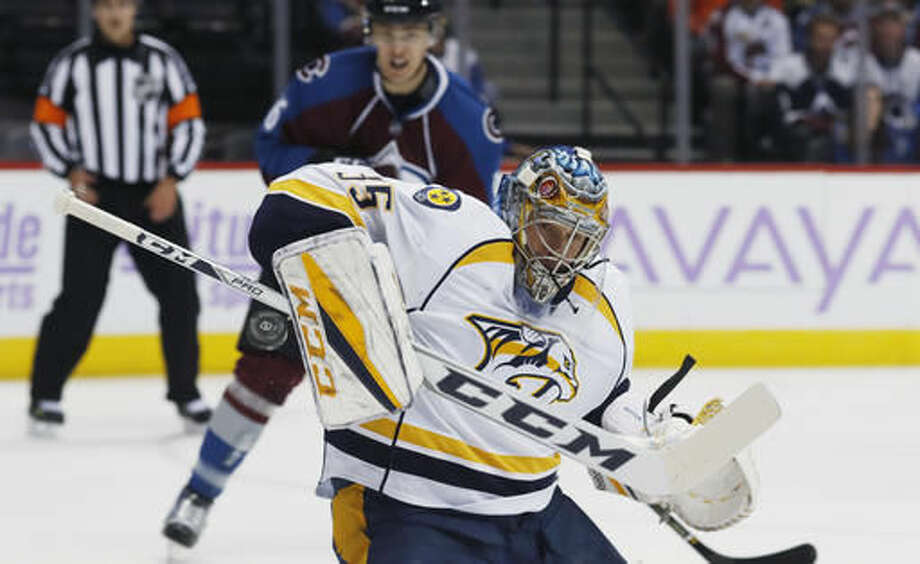 Nashville Predators goalie Pekka Rinne, front, of Finland, deflects a shot as Colorado Avalanche defenseman Erik Johnson watches during the first period of an NHL hockey game Tuesday, Nov. 1, 2016 in Denver. (AP Photo/David Zalubowski)