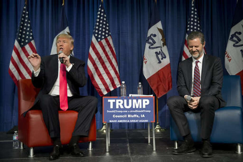 FILE - In a Jan. 31, 2016 file photo, Jerry Falwell Jr., president of Liberty University, smiles as he listens to Republican presidential candidate Donald Trump, left, at a rally, in Council Bluffs, Iowa. Tiny cracks have appeared in evangelical support for Donald Trump in the maelstrom surrounding the newly released 2005 video of his vulgar comments about women. But conservative Christian support for the Republican nominee, which has confounded many inside and outside evangelicalism, seems to be holding for now. (AP Photo/Jae C. Hong, File)