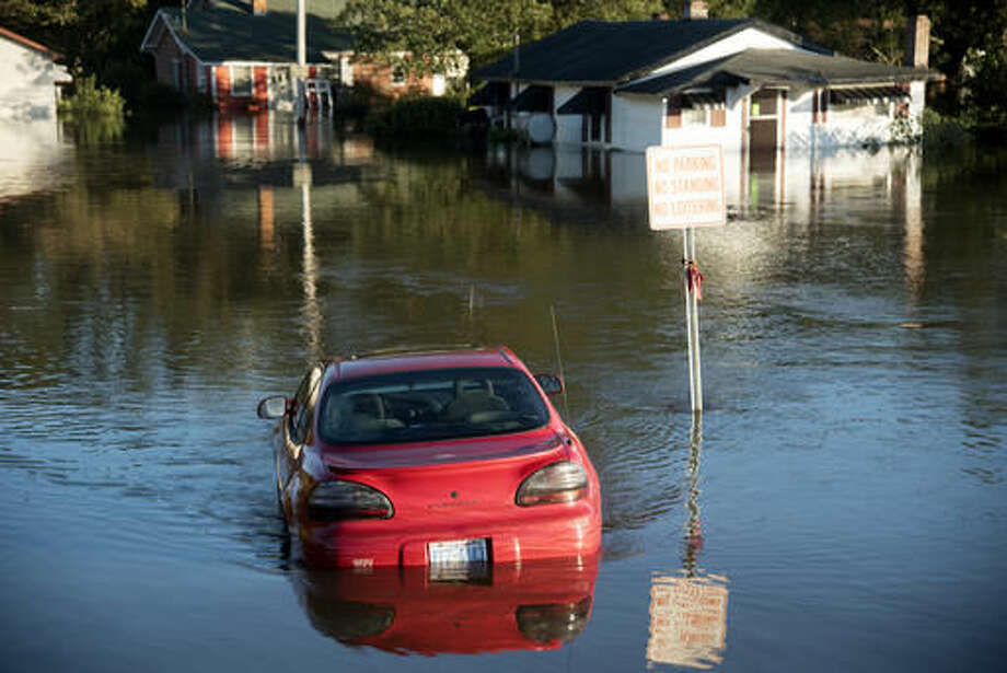 A car is submerged in floodwaters caused by rain from Hurricane Matthew in Lumberton, N.C., Monday, Oct. 10, 2016. (AP Photo/Mike Spencer)