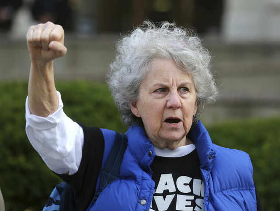 Betty Palme, of Silverton, Ohio, takes part in a protest with the Black Lives Matter group at the Hamilton County Courthouse for the start of the Ray Tensing trial in Cincinnati on Monday, Oct. 31, 2016. A jury of two blacks and 10 whites was seated on Monday for the murder trial of Tensing, a white University of Cincinnati police officer who fatally shot an unarmed black man during a traffic stop last year. (Liz Dufour/The Cincinnati Enquirer via AP)