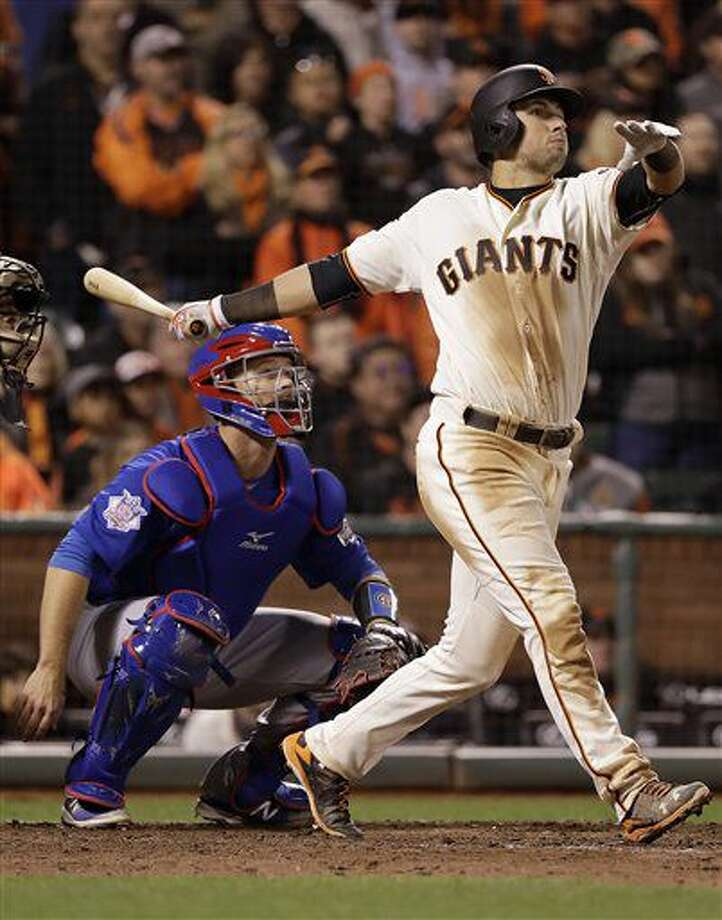 San Francisco Giants' Joe Panik, right, hits a double to score Brandon Crawford in front of Chicago Cubs catcher David Ross during the thirteenth inning of Game 3 of baseball's National League Division Series in San Francisco, Monday, Oct. 10, 2016. The Giants won 6-5 in 13 innings. (AP Photo/Marcio Jose Sanchez)