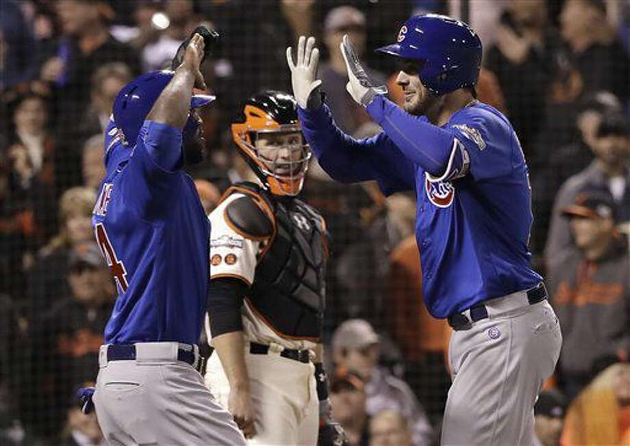Chicago Cubs' Kris Bryant, right, celebrates with Dexter Fowler after hitting a two-run home run as San Francisco Giants catcher Buster Posey, center, watches during the ninth inning of Game 3 of baseball's National League Division Series in San Francisco, Monday, Oct. 10, 2016. (AP Photo/Marcio Jose Sanchez)