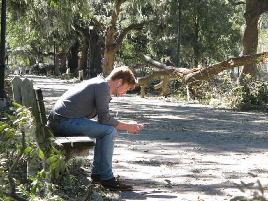 Taylor Henderson sits on a park bench on Monday, Oct. 10, 2016, across a footpath from piles of twisted tree debris that Hurricane Matthew left in Forsyth Park in Savannah, Ga. Hurricane Matthew bushwhack Savannah as it raked the Georgia coast over the weekend, causing extensive damage to the historic city's signature tree canopy. (AP Photo/Russ Bynum)