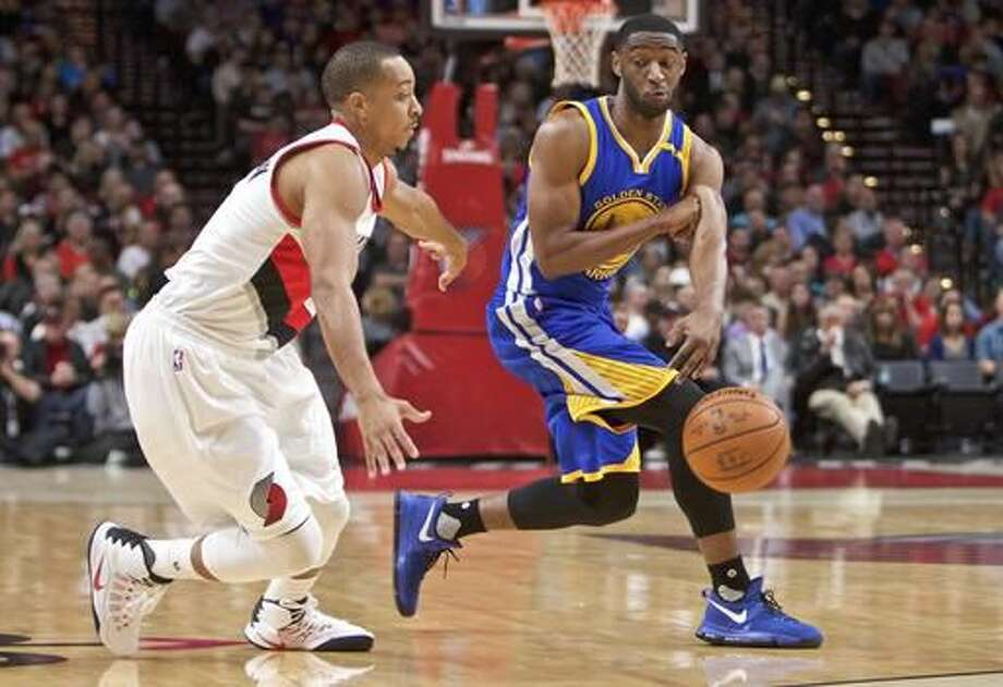 Golden State Warriors guard Ian Clark, right, passes around Portland Trail Blazers guard C.J. McCollum, left, during the first half of an NBA basketball game in Portland, Ore., Tuesday, Nov. 1, 2016. (AP Photo/Craig Mitchelldyer)