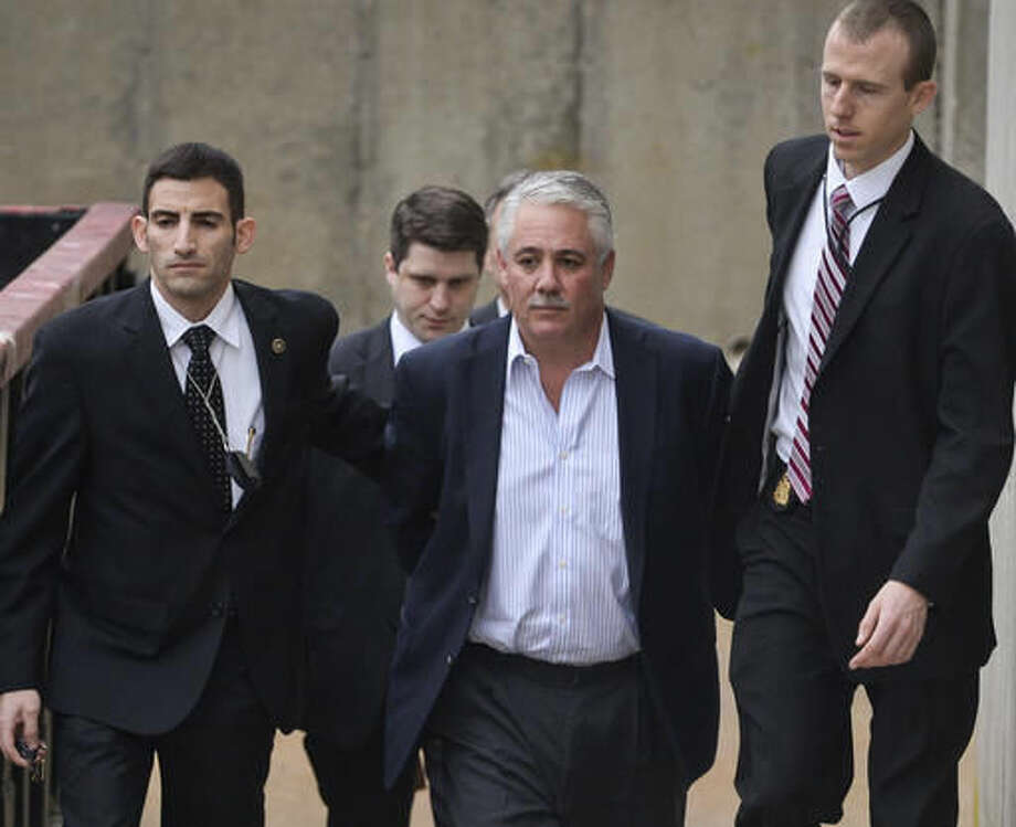 "FILE - In this Dec. 9, 2015 file photo, former Suffolk County Police Chief James Burke is escorted to a vehicle by FBI personnel outside an FBI office in Melville, N.Y. Federal prosecutors say Burke recruited a long list of accomplices to cover up his precinct house beating of a man suspected of stealing embarrassing items from his SUV, and have signaled that more people, including ""high-ranking officials,"" could face charges. Burke is to be sentenced Wednesday, Nov. 2, 2016. (Steve Pfost/Newsday via AP, File)"