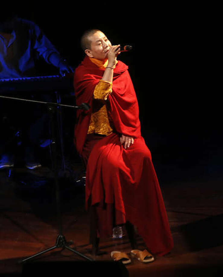 In this Oct. 7, 2016 photo, Buddhist nun and musician Ani Choying Drolma performs during a concert in Mumbai, India. She is one Buddhist nun everyone in Nepal knows by name, not because she's a religious icon and a UNICEF goodwill ambassador, nor for her work running a girl's school and a hospital for kidney patients but because she is one of the country's biggest pop stars. With more than 12 albums of melodious Nepali tunes and Tibetan hymns that highlight themes of peace and harmony, the songstress in saffron robes has won hearts across the Himalayan nation and abroad. (AP Photo/Rajanish Kakade)