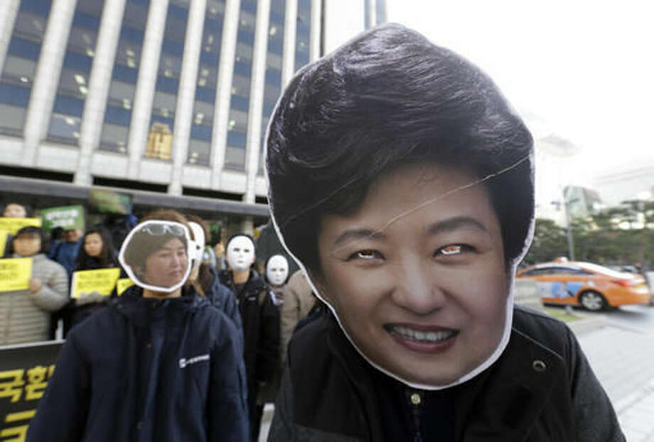 South Korean protesters wearing masks of South Korean President Park Geun-hye, right, and Choi Soon-sil, who is at the center of a political scandal, stage a rally calling for Park to step down in downtown Seoul, South Korea, Wednesday, Nov. 2, 2016. South Korea's embattled president has replaced her prime minister and two other top officials in a bid to restore public confidence amid a political scandal involving her longtime friend. (AP Photo/Ahn Young-joon)