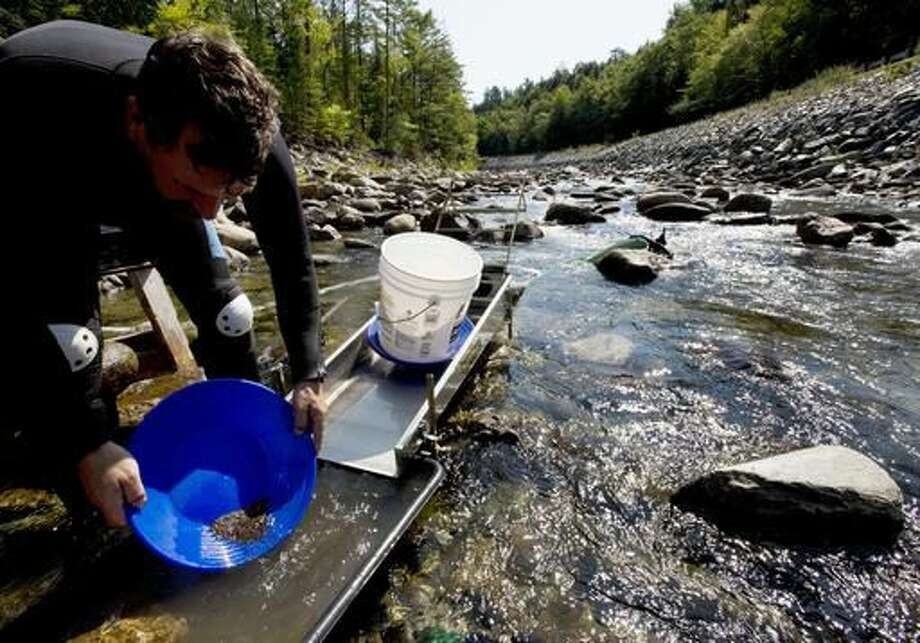 In this photo taken Sunday, Sept. 4, 2016, Chris Hall uses a sluice box to pan for gold in the Wild Ammonoosuc River in Bath, N.H. A new generation of gold miners is giving prospecting a try, especially in New England and the Pacific Northwest. But more are turning to machinery, and that's causing problems. Environmentalists complain mechanized mining poses a threat to river systems. Some states are banning certain mining techniques deemed harmful. (AP Photo/Jim Cole)