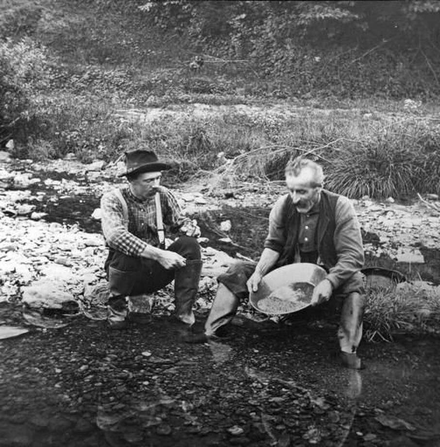In this 1887 photo provided by the Plymouth Historical Society, men pan for gold in a stream in the Five Corners area of Plymouth, Vt. A growing number of people, especially in New England and the Pacific Northwest, are returning to streams in search of gold. (E.G. Davis collection/Plymouth Historical Society via AP)