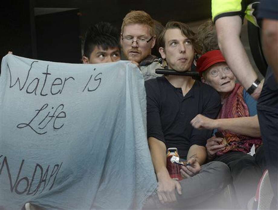 Protesters sit chained together at the Wells Fargo Center building in Salt Lake City during a rally in support of the Standing Rock Sioux against the Dakota Access Pipeline, Monday, Oct. 31, 2016. Wells Fargo is one of several major banks financing the pipeline. (Al Hartmann/The Salt Lake Tribune via AP)