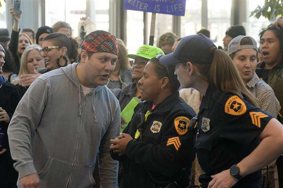 A protester speaks with police officers during a rally in the lobby of the Wells Fargo Center building in Salt Lake City in support of the Standing Rock Sioux against the Dakota Access Pipeline, Monday, Oct. 31, 2016. Wells Fargo is one of several major banks financing the pipeline. (Al Hartmann/The Salt Lake Tribune via AP)