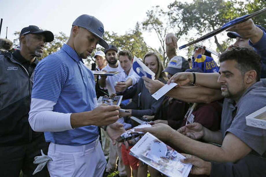 Golden State Warriors' Stephen Curry signs autographs while walking to the 15th tee of the Silverado Resort North Course during the pro-am event of the Safeway Open PGA golf tournament Wednesday, Oct. 12, 2016, in Napa, Calif. (AP Photo/Eric Risberg)