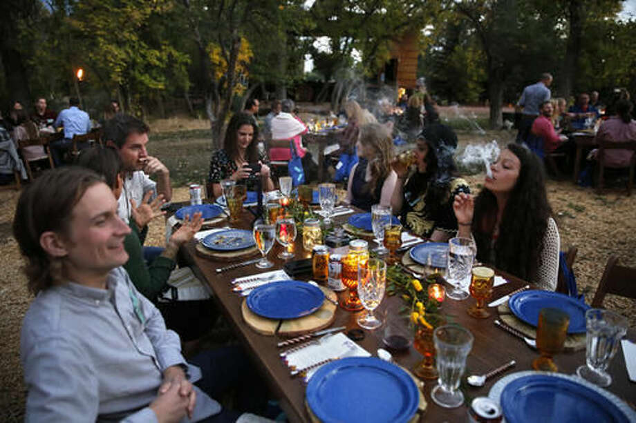 In this Oct. 2, 2016 photo, diners smoke marijuana as they eat dishes prepared by chefs during an evening of pairings of fine food and craft marijuana strains served to invited guests dining at Planet Bluegrass, an outdoor venue in Lyons, Colo. Chefs and pot growers trying to explore fine dining with weed face a legal gauntlet to make pot dinners a reality, even where the drug is legal. (AP Photo/Brennan Linsley)