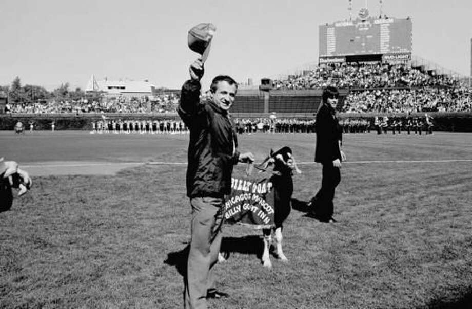 FILE - In this Oct. 2, 1984, file photo, Sam Sianis, center, owner of the Billy Goat Tavern in Chicago, acknowledges the crowd along with his goat before a National League playoff baseball game between the San Diego Padres and the Chicago Cubs in Chicago. Sianis and the goat were invited as guests of the Cubs, both being issued tickets. Every postseason run by the Chicago Cubs is accompanied by a fear of failure for its diehard fans. But young supporters of the Cubs know little of billy goat curses and botched plays, and they are confident of a World Series win. (AP Photo/File)