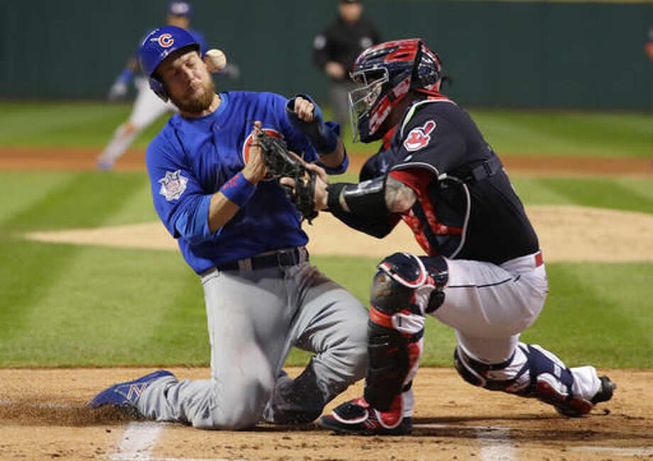 Chicago Cubs' Ben Zobrist collides with Cleveland Indians catcher Roberto Perez as he scores during the first inning of Game 6 of the Major League Baseball World Series Tuesday, Nov. 1, 2016, in Cleveland. (AP Photo/Jamie Squire, Pool)