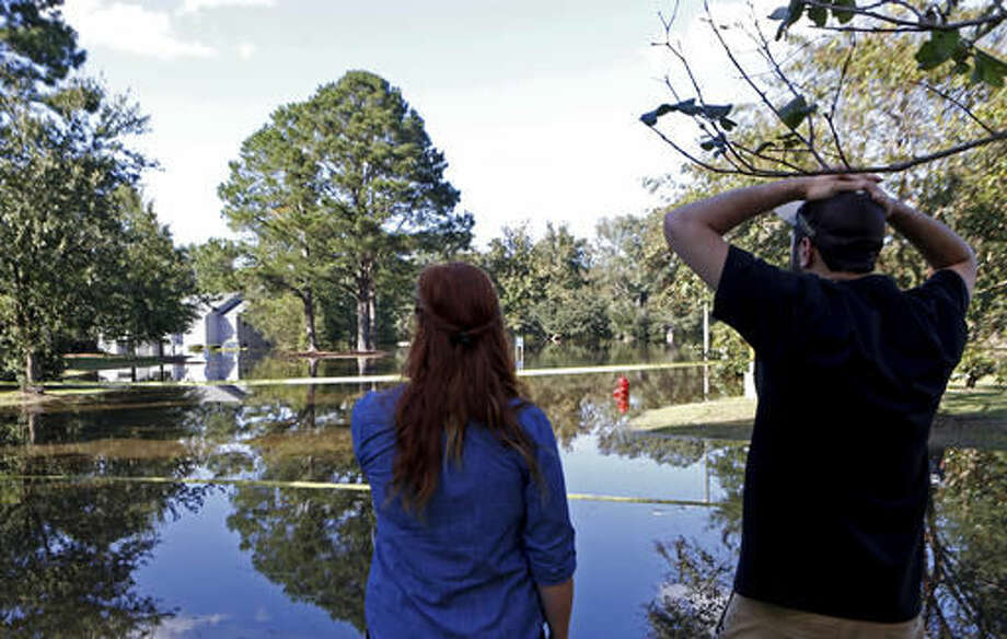 Caitlyn Cain, left, and friend Sidney Daniels inspect flooding associated with Hurricane Matthew near Cain's old home, Wednesday, Oct. 12, 2016, in Greenville, N.C. (AP Photo/Brian Blanco)