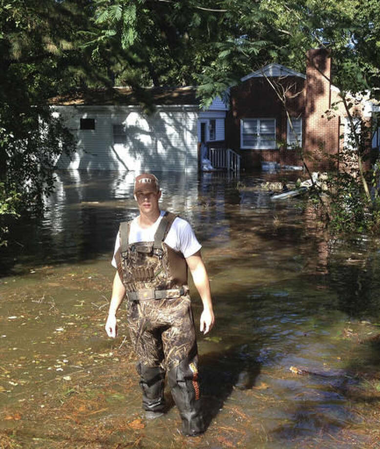 Adam Brauns walks away from a house near the Tar River in Greenville, N.C., where he was using duct tape and sheets of plastic to seal off a crawl space on Wednesday, Oct. 12, 2016. Many houses and apartments near the river were already taking on water a day before the river swollen by Hurricane Matthew was forecast to crest on Thursday. (AP Photo/Jonathan Drew)