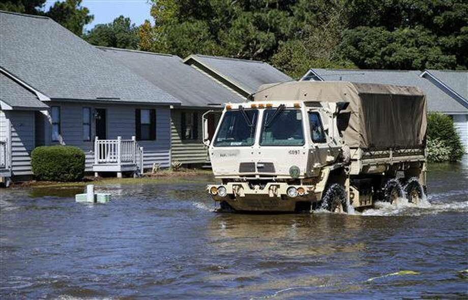 A National Guard vehicle drives through as the floodwaters slowly rise at the Wyndham Circle duplex complex in Greenville, NC on Wednesday, Oct. 12, 2016. The homes were threatened as the Tar River came out of its banks from all the rains from Hurricane Matthew, which passed through the eastern part of the state a few days ago. Some North Carolina rivers, like the Tar, continue to rise from the heavy rains, threatening property and forcing evacuations. (Chris Seward/The News & Observer via AP)