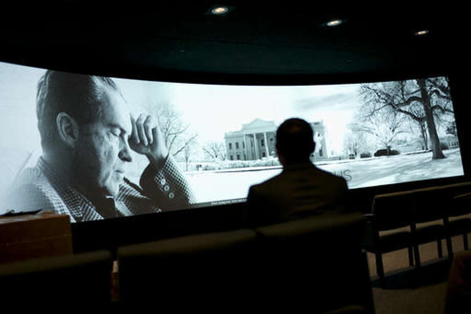 In this Wednesday, Oct. 5, 2016 photo, Joe Lopez, a communications director at Richard Nixon Foundation, watches a film that opens with Nixon's resignation speech after the Watergate scandal at the Richard Nixon Presidential Library and Museum in Yorba Linda, Calif. The museum will reopen Friday, Oct. 14, following a $15 million makeover aimed at bringing the country's 37th president closer to younger generations less familiar with his groundbreaking trip to China or the Watergate scandal. (AP Photo/Jae C. Hong)