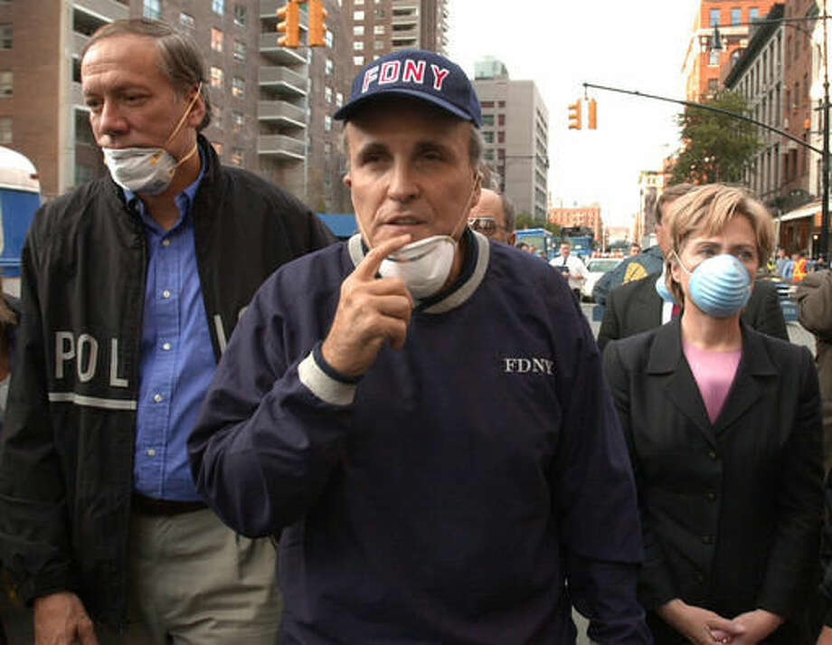 FILE - In this Wednesday, Sept. 12, 2001 file photo, New York City Mayor Rudolph Giuliani, center, leads New York Gov. George Pataki, left, and Sen. Hillary Clinton, D-N.Y., on a tour of the site of the World Trade Center disaster. While stumping for Donald Trump in Ocala, Fla., on Oct. 12, 2016, former New York City Mayor Rudy Giuliani accused Hillary Clinton of falsely claiming to have been in New York on Sept. 11, 2001. It isn't clear what Giuliani was talking about. On many occasions, Clinton has described being in Washington, where Congress was in session, on Sept. 11 when hijacked jets began striking the World Trade Center and the Pentagon. Flights were still grounded on Sept. 12, 2001, but Clinton traveled to New York City the next day aboard a federal plane. There, she circled the smoldering World Trade Center in a helicopter, then toured ground zero with Giuliani and Pataki. (AP Photo/Robert F. Bukaty, File)