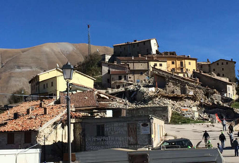 Members of the regional alpine emergency rescue team escort residents to their village of Castelluccio, Italy to inspect the damage, on Tuesday Nov. 1, 2016. Earthquake aftershocks gave central Italy no respite on Tuesday, haunting a region where thousands of people were left homeless and frightened by a massive weekend tremor that razed centuries-old towns. (AP Photo/Matteo Witt)