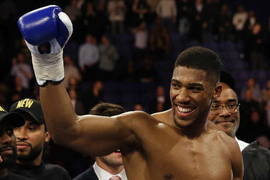 FILE - This is a Saturday, April 9, 2016 file photo of British boxer Anthony Joshua as he celebrates after winning the IBF heavyweight title bout against US boxer Charles Martinat the O2 Arena in London. Joshua will make the second defense of his IBF world heavyweight title in a fight against American boxer Eric Molina on Dec. 10. Joshua's promoters announced the fight on Tuesday Nov. 1, 2016. (AP Photo/Matt Dunham, File)