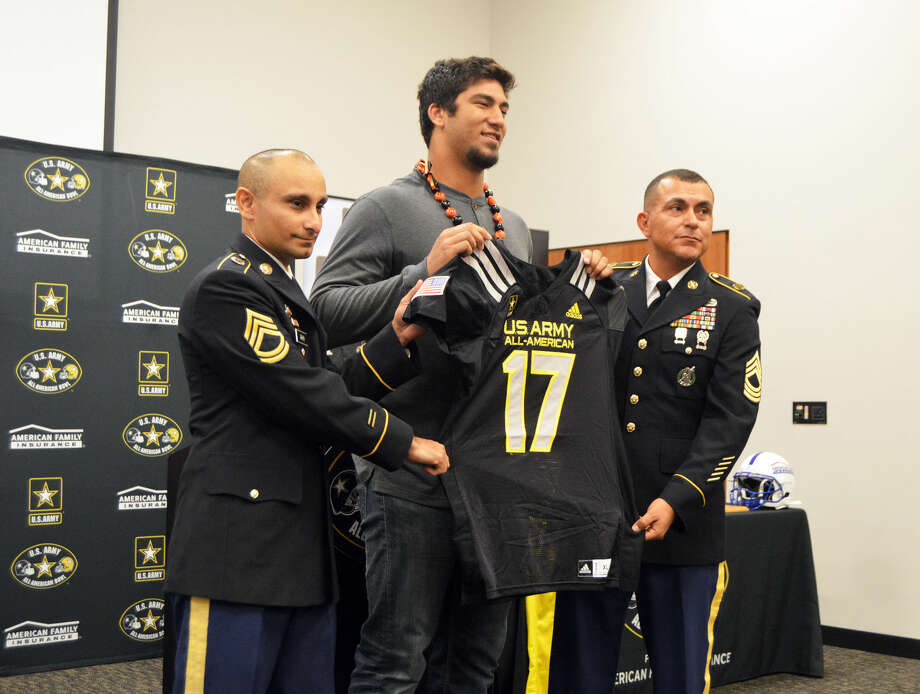 Edwardsville senior AJ Epenesa, center, receives his jersey for the U.S. Army All-American Bowl from two members of the Army at the Jon Davis Wrestling Center.
