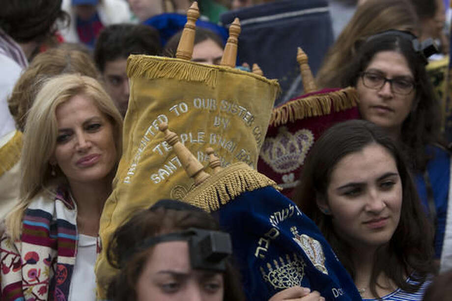 Women hold Torah scrolls as they pray at the Western Wall, the holiest site where Jews can pray in Jerusalem's Old City, Wednesday, Nov. 2, 2016. Leaders of liberal Jewish movements in the U.S. and Israel have demonstrated for equal prayer at a Jewish holy site, despite a plea from Israel's prime minister not to push the matter publicly. (AP Photo/Sebastian Scheiner)