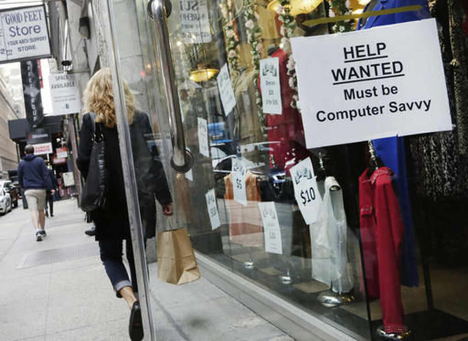 "FILE - In this Oct. 1, 2015, file photo, a shopper walks past a store with a ""Help Wanted"" sign in the window, in New York. On Wednesday, Nov. 2, 2016, payroll processor ADP reports on the number of jobs private employers added in October. (AP Photo/Mark Lennihan, File)"