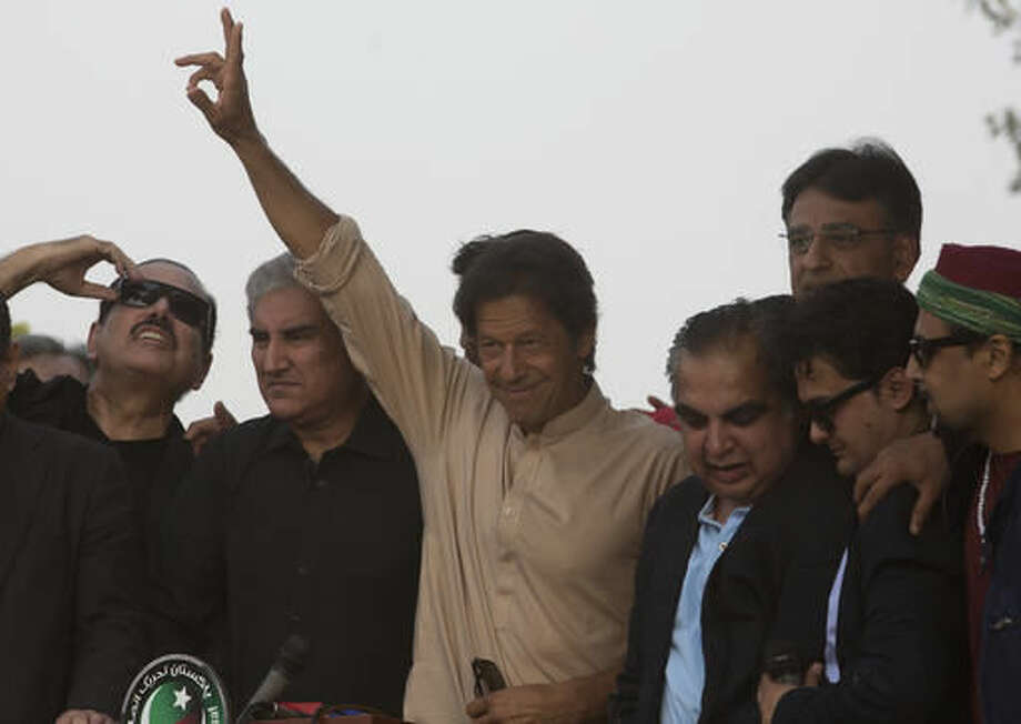 Pakistani opposition leader Imran Khan flashes a victory sign outside his residence in Islamabad, Pakistan, Tuesday, Nov. 1, 2016. Khan has called off a mass protest aimed at shutting down the capital and forcing the resignation of the prime minister. (AP Photo/B.K. Bangash)