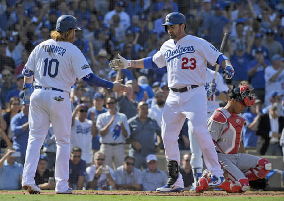 Los Angeles Dodgers' Adrian Gonzalez (23) celebrates with Justin Turner, left, after hitting a two-run home run as Washington Nationals catcher Pedro Severino looks away during the first inning in Game 4 of baseball's National League Division Series in Los Angeles, Tuesday, Oct. 11, 2016. (AP Photo/Mark J. Terrill)